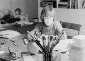 Here I am as a child writing at my mother's drawing table in the living room.  Notice her paintbrushes.  My mom was always working on some creative project.  Like mother. Like daughter.